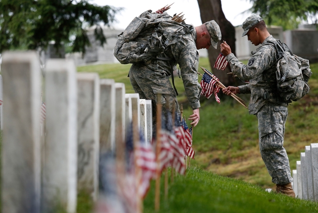 ARLINGTON, VA - MAY 21:  Members of the 3rd U.S. Infantry Regiment place American flags at the graves of U.S. soldiers buried at Arlington National Cemetery, in preparation for Memorial Day May 21, 2015 in Arlington, Virginia.